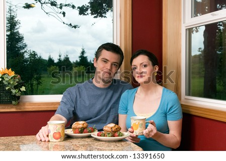 A couple eating continental breakfast at home. - stock photo