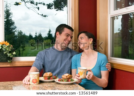 A couple eating continental breakfast at home looking at each other. - stock photo