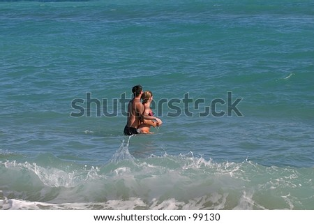 A couple embraces in the ocean. - stock photo