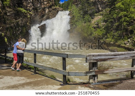 A couple enjoy the fast flowing waterfall at Cameron Falls in Waterton Lakes National Park. - stock photo