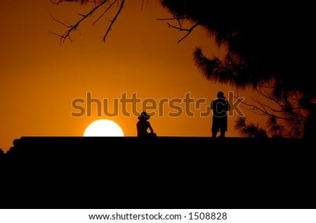 a couple enjoying a romantic sunset - stock photo