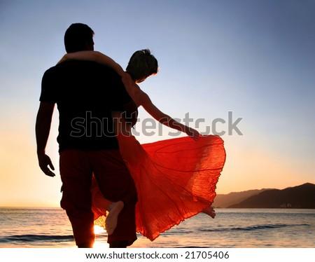 A couple enjoying sunset on the beach - stock photo