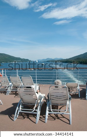 A couple enjoying the scenery from the upper deck of a cruise ship in Alaska.