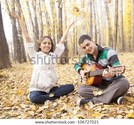 A couple enjoying themselves in autumn forest with a guitar  the guy playing the acoustic guitar and the girl throws up on a dry yellow poplar leaves