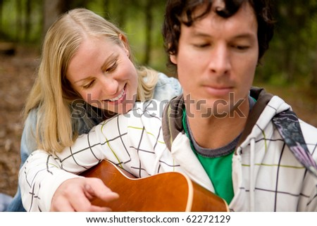 A couple enjoying themselves outdoors with a guitar, focus on woman - stock photo