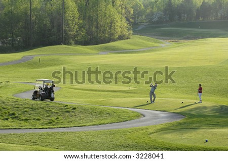 a couple goes golfing in late afternoon