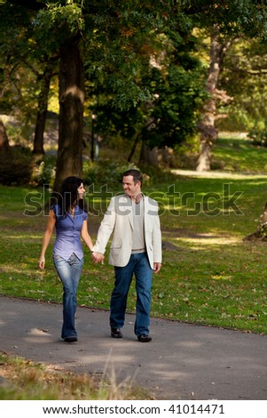 A couple happy and walking in a park - stock photo