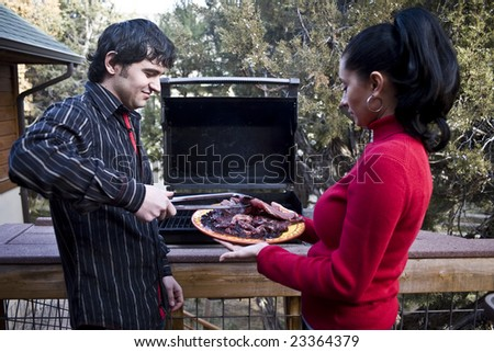 A couple having a barbeque on the patio at home - stock photo