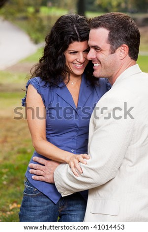 A couple having fun and laughing in the park - stock photo