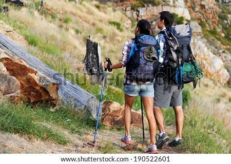 A couple hiking along a mountain path - stock photo