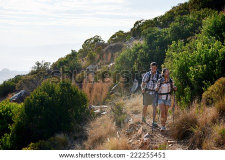A couple hiking in the great outdoors along a trail in nature - stock photo