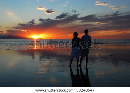 A couple hold hands during a sunset - stock photo