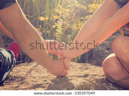 a couple holding hands in the rays of sunlight during sunrise or sunset with copy space with a retro instagram toned filter - stock photo