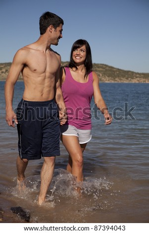 A couple holding hands walking in the water together looking up at each other. - stock photo