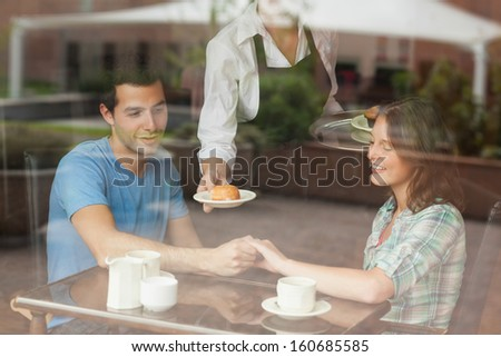 A couple holding hands while waitress serving food in college canteen - stock photo