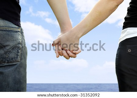 A couple holds hands in a park - stock photo