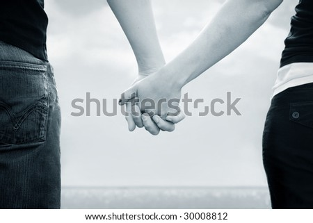 A couple holds hands in front of the sea