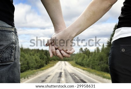 A couple holds hands on a country road - stock photo