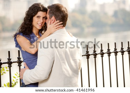 A couple hugging in the park - eye contact with the female - stock photo