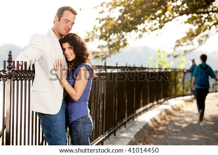 A couple hugging in the park on a path - stock photo