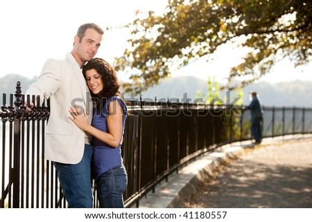 A couple huggnig in the park on a path - stock photo