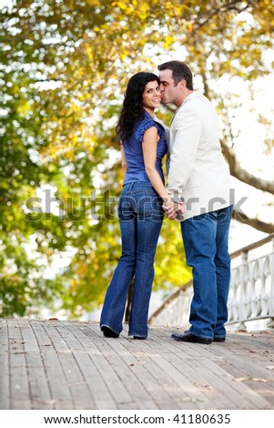A couple in a park with the man kissing the woman - stock photo