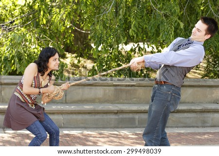 A couple in a playful game of tug of war. - stock photo