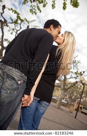 A couple in an urban European city setting kissing - stock photo