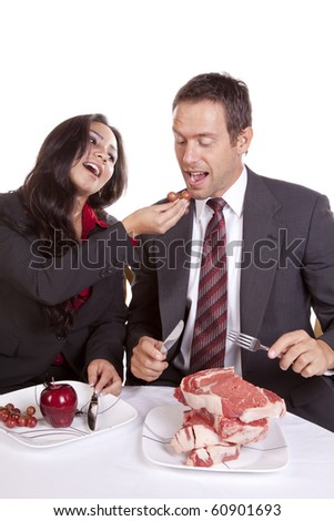 A couple in business attire eating.  She is feeding him grapes. - stock photo