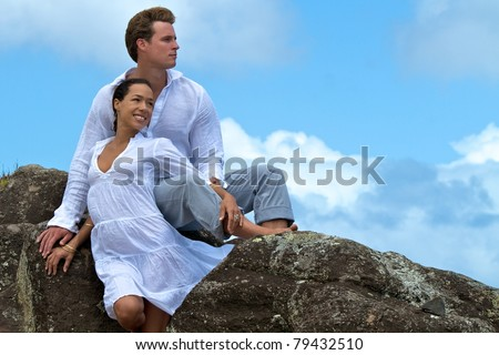 A couple in Hawaii look into the distance, as they relax atop these cliffside rocks overlooking the ocean on the island of Maui. - stock photo