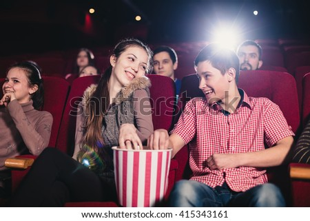 A couple in love flirting at the cinema and eating popcorn - stock photo
