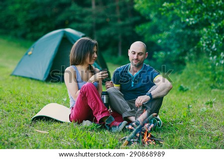 a couple in love is sitting at the fire and drinking tea