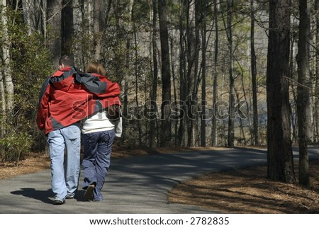 A couple in love walks together down a forest path