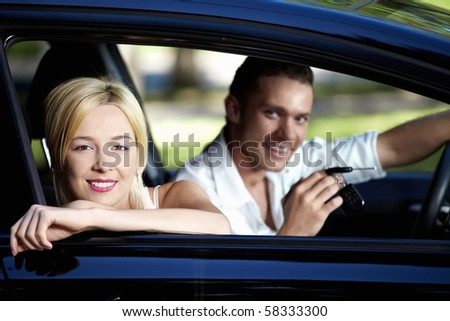 A couple in the car with the keys of her - stock photo