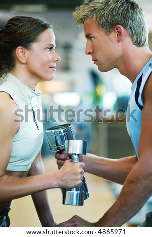 A couple in the gym, rivaling each other, exercising with weights - stock photo