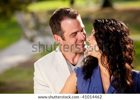 A couple in the park happy and about to kiss - stock photo