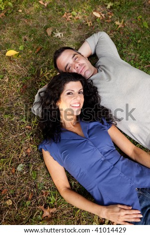 A couple in the park laying on the grass.  Sharp focus on female. - stock photo