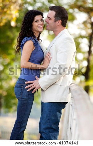A couple in the park with the man smiling at the woman - stock photo