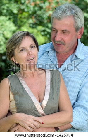 A couple in their 50s standing while the man embraces the woman. - stock photo
