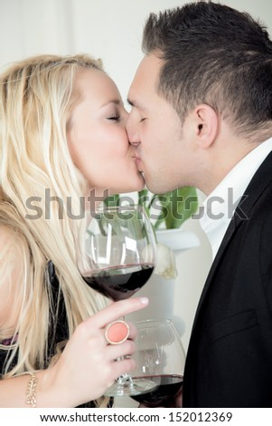 A couple is kissing while celebrating there first date with a glass of red wine. - stock photo