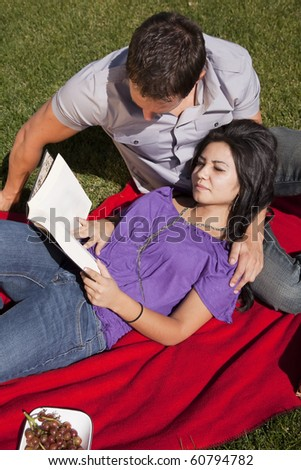 A couple is laying on a blanket reading a book.