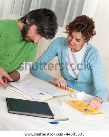 A couple is looking through a notebook full of ideas to design their new home.
