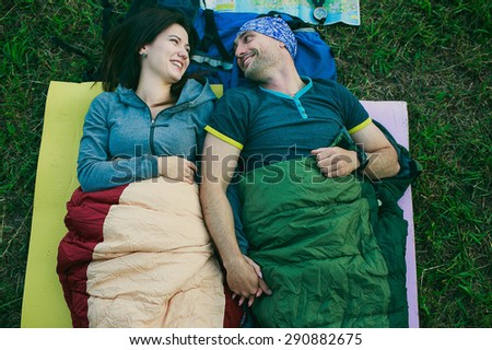a couple is lying in a sleeping bags in the mountains - stock photo