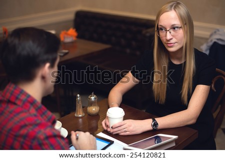 A couple is on a date in a cafe drinking coffee, girl is listening carefully with interest - stock photo