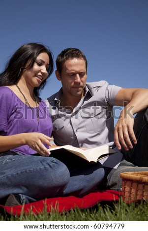 A couple is on a red blanket reading a book by a picnic basket.