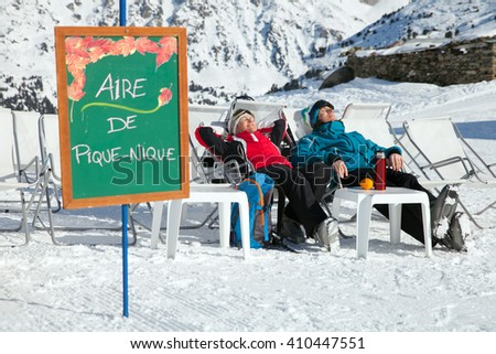 A couple is resting on lounges in picnic zone on european ski resort - stock photo