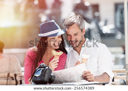 A couple is sitting at an outside bar table eating ice creams and looking at a map. The grey hair man with a beard is holding the map. The woman is wearing a blue hat, there is a camera on the table  - stock photo