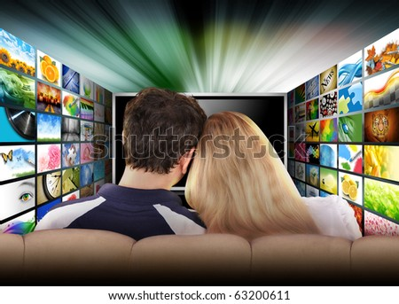 A couple is sitting on a couch watching a flat screen television with photo images. The tv has a glowing light coming out the top. Use it for a media, entertainment, technology or date night concept. - stock photo