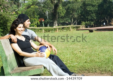 A couple is sitting on a park bench. Horizontally framed photo. - stock photo