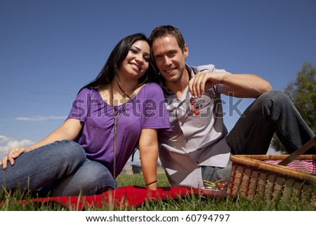 A couple is sitting on a red blanket eating grapes outdoors. - stock photo